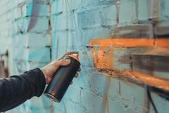 cropped view of street artist painting colorful graffiti on wall royalty free stock photography