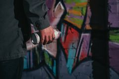 cropped view of street artist painting graffiti with aerosol paint on wall stock images