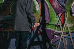 cropped view of street artist painting graffiti with aerosol paint on wall stock photography