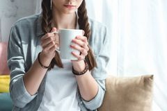 cropped view of teen girl with cup stock image