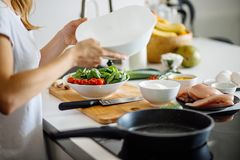 Woman making healthy salad from fresh vegetables. Cropped view of woman hands slicing chicken breasts meat on chopping board, preparing dinner for beloved Royalty Free Stock Images