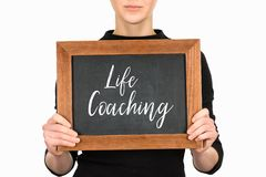 Cropped view of woman holding board with lettering life couching Stock Photo