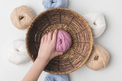 Woman holding pink yarn ball in hand in wicker basket on white background. Cropped view of woman holding pink yarn ball in hand in wicker basket on white Stock Photos