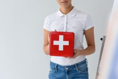 cropped view of woman presenting red first aid kit, royalty free stock photo