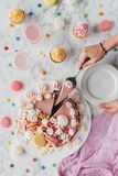 cropped view of woman putting piece of pink birthday cake with marshmallows royalty free stock image