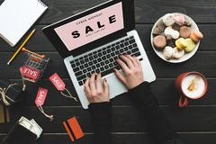 Online shopping with laptop. Cropped view of woman shopping online with credit card and laptop on table with macarons, coffee and sale tags vector illustration