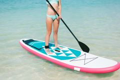 Cropped view of woman on stand up paddle board on sea. At tropical resort Royalty Free Stock Images