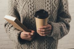 Woman in sweater with book and coffee. Cropped view of woman in sweater holding book and coffee to go Stock Image