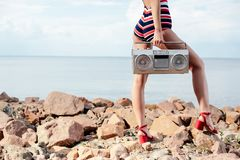 Cropped view of woman in swimsuit holding vintage boombox on rocks. Near the sea stock photo
