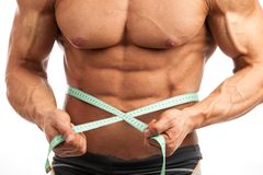Cropped view of young muscular man with measuring tape. Around his waist Royalty Free Stock Images