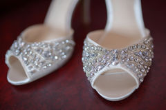 Cropped, white silk bridal peep toe shoes with rhinestones and delicate beads, displayed fully, in pair, on a dark red background Royalty Free Stock Images