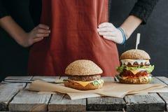 cropped widok dziewczyna w fartuch pozyci przy drewnianym stołem z domowej roboty cheeseburgers obrazy stock