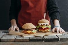 cropped widok dziewczyna w fartuch pozyci przy drewnianym stołem z smakowitymi cheeseburgers fotografia stock