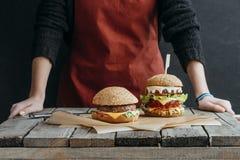 cropped widok dziewczyna w fartuch pozyci przy drewnianym stołem z smakowitymi hamburgerami obrazy royalty free