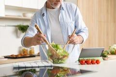 Cropped wizerunek dojrzałego mężczyzna kulinarna sałatkowa używa pastylka zdjęcie royalty free