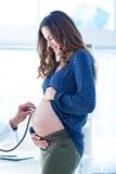 Cropped wizerunek doktorski egzamininuje kobieta w ciąży brzuch w klinice Zdjęcie Stock