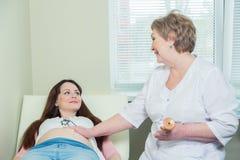 Cropped wizerunek doktorski używa stetoskopu biały egzamininuje kobieta w ciąży w klinice Zdjęcia Stock