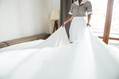 Cropped wizerunek hotel gosposia zmienia łóżkowego prześcieradło obraz stock