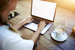 Cropped wizerunek kobiety ręki keyboarding na książce podczas gdy siedzący przy drewnianym stołem w kawiarni Fotografia Royalty Free