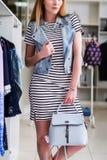 Cropped wizerunek kobiety wzorcowa jest ubranym paskująca suknia, drelichowa kamizelka i torebka od lato kolekci w moda butiku, fotografia royalty free