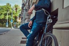Cropped wizerunek modny mężczyzna w eleganckich ubraniach opiera przeciw ścianie z miasto bicyklem na ulicie obraz royalty free