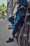 Cropped wizerunek modny mężczyzna w eleganckich ubraniach opiera przeciw ścianie z miasto bicyklem na ulicie fotografia royalty free