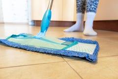 Cropped wizerunek piękna młoda kobieta używa błękitnego kwacz w kuchni podczas gdy czyścić podłoga zdjęcia stock