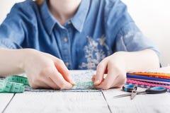 Cropped wizerunek piękny młody projektant pracuje z nakreśleniami i miarą taśmy w dressmaking salonie Zdjęcia Stock