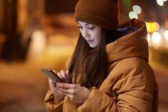 Cropped wizerunek przyjemna przyglądająca kobieta koncentrująca w mądrze telefonie, ubierającym w eleganckim kłobuku i kurtce, pl fotografia royalty free