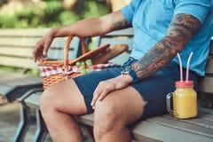 Cropped wizerunek tatuująca męska jest ubranym koszula i skróty siedzi z pyknicznym szkłem sok pomarańczowy na a i koszem fotografia royalty free