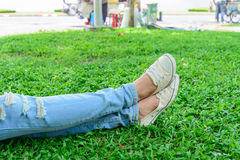 Cropped woman legs in denim with white sneakers resting on grass Stock Photos