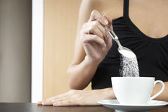 Cropped Woman Pouring Sugar In Tea Cup. Closeup of a cropped woman pouring sugar into tea cup Stock Photos