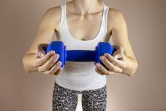 Cropped woman in white shirt with dambbell in her hands clase up. Slimming diet and fitness concept stock photos