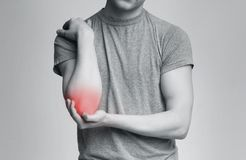 Cropped young man suffering from painful elbow. Arm pain and injury concept. Man with painful elbow, black and white photo with red accent on trauma stock images