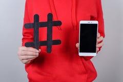 Cropped zbliżenie fotografia ludzie osoby mienia demonstruje pokazywać czerń krzyżował hashtag w ręce i białym mądrze telefonie o zdjęcie royalty free