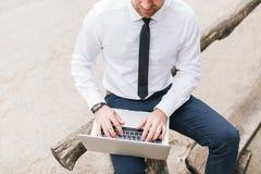 Croppes a tiré du mâle beau futé dans la chemise blanche se reposant à la table en bois utilisant le PC et la radio d'ordinateur  images stock