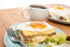 Croque Madame with Coffee. Two Servings of Croque Madame - Ham, Cheese, Bechamel Sauce and Egg Toasted Sandwich garnished with fresh green lettuce salad and a Royalty Free Stock Photo