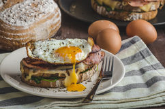 Croque madame. Delicious french breakfast with ham, cheese, egg and spinach with garlic Royalty Free Stock Image