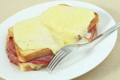 Croque monsieur at an angle. Croque monsieur, a traditional French ham and cheese toastie topped with bechamel sauce and melted cheese on a plate with a fork Stock Photography