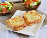 Croque-monsieur with green salad. On a white plate royalty free stock photos