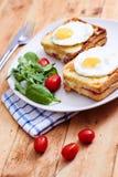 Croque Monsieur mit Eiern auf Weinlesetabelle Stockbild