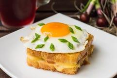 Croque-signora, un panino francese con i verdi e succo della bacca per la tavola di legno della prima colazione Vista superiore P Immagini Stock