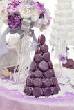 Croquembouch macaron wedding cake. Beautiful purple croquembouch macaron wedding cake together with bridal bouquet and champagne glass on table. Winter style Stock Photography