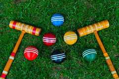 Croquet balls and mallets. On green grass background Royalty Free Stock Images