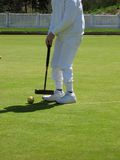 Croquet in Play. A croquet player about to strick the ball Stock Image