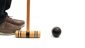 Croquet situation. Closeup of feet croquet mallet and ball over white Stock Photos