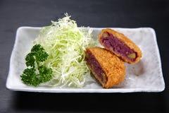 Croquete roxo da batata doce em uma mesa de jantar foto de stock royalty free