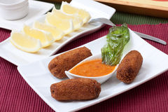 Croquettes. Chicken fried croquettes on white platter with basil leaf stock photo