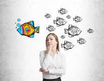 Croquis blonds de fille et de poissons sur le mur en béton Image stock