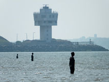 Crosby beach. With public anthony gormley sculptures and industrial buildings Royalty Free Stock Images